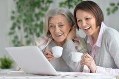 hija de la madre y del adulto con el ordenador portátil Foto de archivo