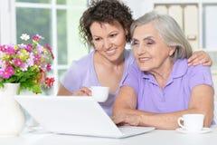 hija de la madre y del adulto con el ordenador portátil Imagenes de archivo