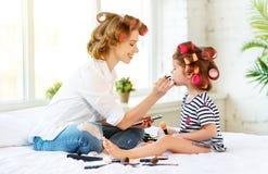 Hija de la madre y del bebé en los bigudíes que hacen maquillaje en cama Imagen de archivo