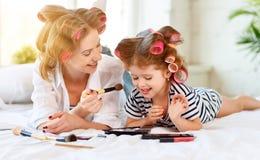 Hija de la madre y del bebé en los bigudíes que hacen maquillaje en cama Fotografía de archivo libre de regalías