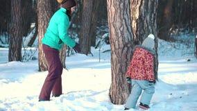 Hija de la madre y del bebé que juega y que ríe en invierno al aire libre en la nieve metrajes