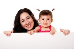 Hija de la madre y del bebé que lleva a cabo a la tarjeta blanca foto de archivo libre de regalías