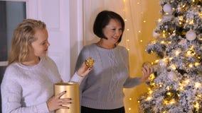 Hija de la mamá junto que adorna el árbol de navidad en sala de estar en la víspera del día de fiesta almacen de metraje de vídeo