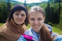 Hija de la mamá y del adulto que se sienta en el top de montañas y que toma el selfie fotos de archivo