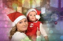 Hija de la mamá y del bebé en la Navidad Foto de archivo