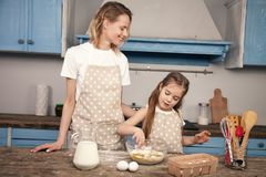 Hija de la mam? y del ni?o en la cocina que prepara la pasta, galletas que cuecen La mam? ense?a a su hija a amasar la pasta de imagen de archivo libre de regalías
