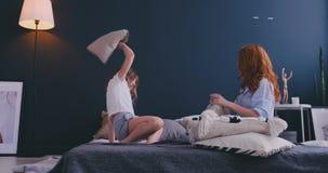 Hija de la mamá y del niño que tiene lucha de almohada junto, niñera joven de la niñera que juega al juego divertido con la mucha metrajes
