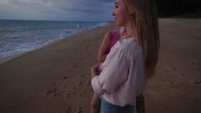 Hija de la ventaja de la madre de la cámara lenta para ver puesta del sol en la playa almacen de video