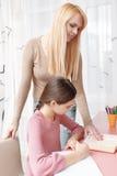 Hija de las ayudas de la madre con el trabajo del hogar Fotografía de archivo