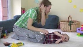 Hija de las cosquillas de la madre pequeña en el sitio lleno de juguetes del bebé 4K almacen de video