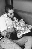Hija de las mamáes que lee un libro que miente en el sofá Fotos de archivo libres de regalías