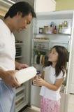 Hija de Pouring Milk For del padre por el refrigerador en cocina Imagenes de archivo