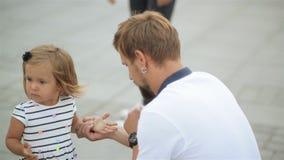 Hija de Sitting Near His del padre barbudo joven pequeña y barrido de sus manos almacen de metraje de vídeo