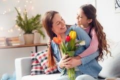 Hija del día de madre de la madre y de la hija en casa que abraza a la madre con el ramo de flores felices fotografía de archivo libre de regalías