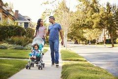 Hija del empuje de la pareja en cochecito como caminan a lo largo de la calle fotografía de archivo libre de regalías