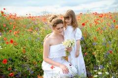 Hija del niño que abraza a su madre entre las flores del campo Imágenes de archivo libres de regalías