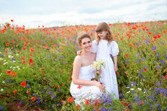 Hija del niño que abraza a su madre hermosa entre la flor roja Imágenes de archivo libres de regalías