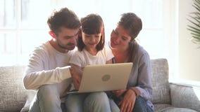 Hija del niño que ríe mirando historietas de observación del ordenador portátil con los padres almacen de video