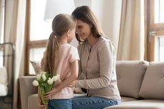 Hija del niño que sostiene los tulipanes que felicitan a la mamá feliz con día de madres imagen de archivo libre de regalías