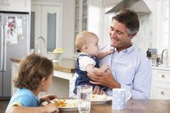 Hija del padre, del hijo y del bebé que tiene comida en cocina junto imagen de archivo