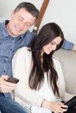 Hija del padre y del adolescente que usa smartphone y la tableta de los dispositivos electrónicos Fotografía de archivo libre de regalías