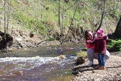 Hija del paseo con su madre en la naturaleza cerca del agua imagen de archivo