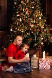 Hija del ` s del papá que sopla hacia fuera velas en un árbol de navidad Imagenes de archivo