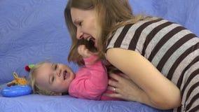 Hija dulce del bebé de las cosquillas felices de la madre en el sofá interior 4K almacen de video