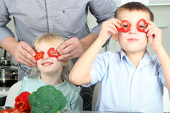Hija e hijo lindos sonrientes que cocinan una cena Pequeños niños que juegan con pimienta colorida con el padre Imagen de archivo libre de regalías