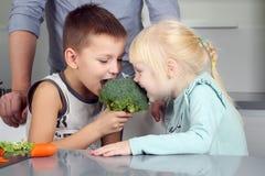 Hija e hijo lindos sonrientes que muerden un bróculi Pequeños niños que juegan con vegatable con el padre Imagen de archivo libre de regalías