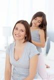 Hija encantadora que aplica su pelo de la mujer con brocha Foto de archivo
