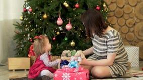 Hija feliz de la familia, de la madre y del niño cerca del árbol de navidad adornado con los regalos que juegan con los juguetes  almacen de video