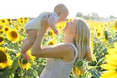 Hija feliz de la madre y del bebé en campo del girasol Foto de archivo