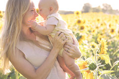 Hija feliz de la madre y del bebé en campo del girasol Foto de archivo libre de regalías