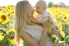 Hija feliz de la madre y del bebé en campo del girasol Fotos de archivo libres de regalías