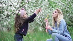 Hija feliz de la mam? y del beb? que juega con las burbujas de jab?n en jard?n floreciente, c?mara lenta metrajes