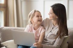 Hija feliz de la mamá y del niño que ríe divirtiéndose con el ordenador portátil foto de archivo