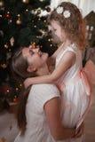 Hija feliz del abrazo de la madre en el árbol de navidad imagenes de archivo