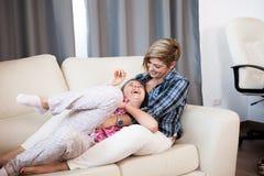 Hija feliz del niño adolescente y su madre que ríen en el sofá Fotos de archivo