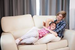 Hija feliz del niño adolescente y su madre que ríen en el sofá Imagenes de archivo