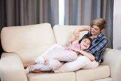 Hija feliz del niño adolescente y su madre que ríen en el sofá Fotografía de archivo libre de regalías