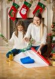 Hija feliz y madre que envuelven el suéter en papel de embalaje en Foto de archivo
