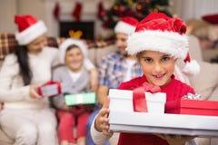 Hija festiva que sostiene la pila de regalos con su familia detrás Imagen de archivo