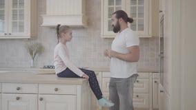 Hija linda que se sienta en la tabla que está atenta su historia emocional de los padres y que tiene torether de la diversión en  almacen de video