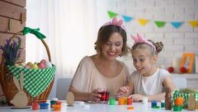 Hija linda que sumerge el huevo en el vidrio con el colorante alimentario rojo, tradiciones de Pascua almacen de metraje de vídeo