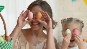 Hija linda y madre que se divierten que pone los huevos coloreados en los ojos, víspera de Pascua almacen de video