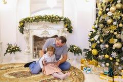Hija linda y papá del papá que juegan en la tableta que se sienta en el piso i Imagen de archivo libre de regalías