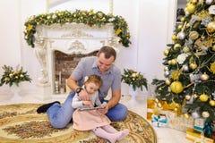 Hija linda y papá del papá que juegan en la tableta que se sienta en el piso i Imágenes de archivo libres de regalías