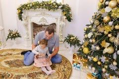 Hija linda y papá del papá que juegan en la tableta que se sienta en el piso i Imagenes de archivo