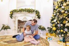 Hija linda y papá del papá que juegan en la tableta que se sienta en el piso i Fotografía de archivo libre de regalías